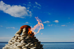 Signal Light. Torch at top of a pyramid from small stones Stock Images