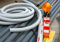 Signal light and plastic pipes for laying optical fiber. Signal light and grey plastic pipes for laying optical fiber in the city Royalty Free Stock Photography