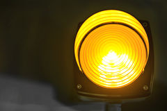 Signal light. Yellow glowing signal warning light royalty free stock photo