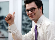 Signal of success. Attractive businessman gives the thumbs up gesture Royalty Free Stock Photos