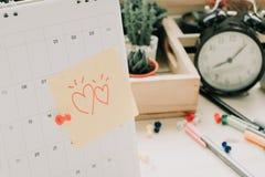 Signalez le papier de note avec le coeur de couples collant sur le calendrier et les affaires Photos stock