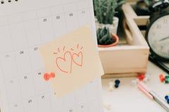 Signalez le papier de note avec le coeur de couples collant sur le calendrier et les affaires Photos libres de droits