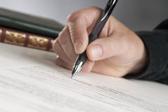 Signature. Man's hand holding a pen writing his signature Stock Photography