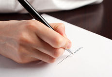 Signature. Female hand signing contract on the table royalty free stock photos
