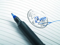 Signature. A signature with a stamp and a blue pen Royalty Free Stock Images
