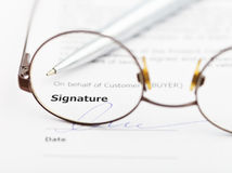 Signature of agreement and pen through eyeglasses Stock Photography