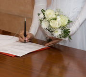 The signature of the bride. The bride with a bouquet signs the document Stock Photo