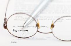Signature of contract and pen through eyeglasses. Signature of sales contract and silver pen through eyeglasses Stock Photography