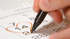 Signature d'un jour du ` s de Valentine sur un calendrier par le coeur rouge de stylo Photo stock