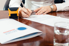 Signature document. Businesswoman signature document, working at her office Royalty Free Stock Image