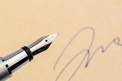 Signature and pen. A fountain pen and a signature on yellow paper. symbolic photo for contract, and graphology testament Royalty Free Stock Photography