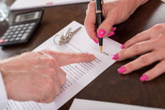 Signature of a real estate contract. Realtor showing where to sign the contract (random english dummy text used Royalty Free Stock Photos
