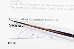 Signature of sales agreement and silver pen Royalty Free Stock Photos
