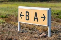 Signaux de direction jaunes et noirs d'aéroport dirigeant des pistes de roulement Images libres de droits
