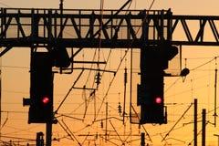 Signaux ferroviaires au rouge au coucher du soleil Photos libres de droits