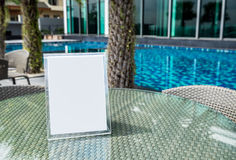 Signboard blank on glass table at pool Royalty Free Stock Image