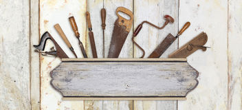Signboard and carpenter tools on wooden background. Signboard and carpenter tools on wooden grunge background Royalty Free Stock Photography