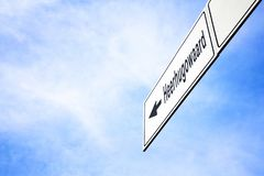 Signboard pointing towards Heerhugowaard. White signboard with an arrow pointing left towards Heerhugowaard, Netherlands, against a hazy blue sky in a concept of royalty free stock image