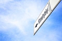 Signboard pointing towards Khmelnytskyi. White signboard with an arrow pointing left towards Khmelnytskyi, Ukraine, against a hazy blue sky in a concept of royalty free stock photography