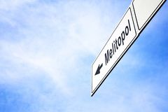 Signboard pointing towards Melitopol. White signboard with an arrow pointing left towards Melitopol, Ukraine, against a hazy blue sky in a concept of travel stock photography