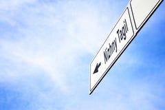 Signboard pointing towards Nizhny Tagil. White signboard with an arrow pointing left towards Nizhny Tagil, Sverdlovsk Oblast, Russia, against a hazy blue sky in stock photo