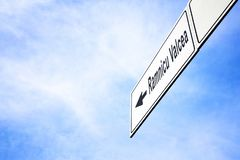 Signboard pointing towards Ramnicu Valcea. White signboard with an arrow pointing left towards Ramnicu Valcea, Romania, against a hazy blue sky in a concept of stock image