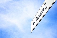 Signboard pointing towards Satu Mare. White signboard with an arrow pointing left towards Satu Mare, Romania, against a hazy blue sky in a concept of travel vector illustration