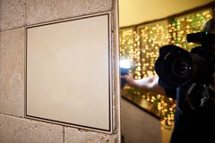 Signboard on a stone wall and the reflection of the photographer with a camera in the mirror royalty free stock image