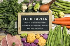 Raw vegetables, eggs and meat and text flexitarian. A signboard with the text flexitarian and its definition on a pile of some different raw vegetables, such as royalty free stock photos