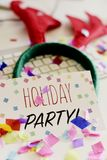 Signboard with text holiday party on office desk. A signboard with the text holiday party, on an office desk full of confetti, next to a reindeer antlers royalty free stock photography