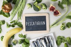 Vegetables, fruit, sardines and text pescatarian. A signboard with the text pescatarian, for vegetarian people who eat fish, and a pile of some different fruits royalty free stock images
