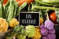 Raw vegetables and text raw veganism. A signboard with the text raw veganism placed on a pile of some different raw vegetables, such as cauliflower of different stock image