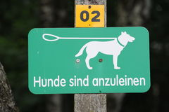 Signboard to leash a dog Royalty Free Stock Photo