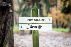 Signboard with two signs saying - Try again - Give up - pointing. In opposite directions with the sign saying Give up scribbled through stock photo