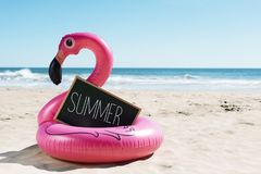 Flamingo swim ring on the beach and text summer. A signboard with the word summer written in it and a swim ring in the shape of a pink flamingo, on the sand of a Stock Photography