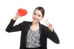 Signe asiatique de victoire d'exposition de femme d'affaires avec le coeur rouge Image stock