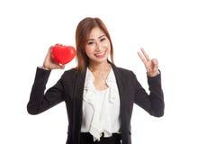 Signe asiatique de victoire d'exposition de femme d'affaires avec le coeur rouge Photo stock