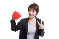 Signe asiatique de victoire d'exposition de femme d'affaires avec le coeur rouge Photo libre de droits