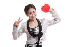 Signe asiatique de victoire d'exposition de femme d'affaires avec le coeur rouge Photos stock