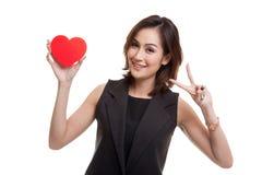 Signe asiatique de victoire d'exposition de femme d'affaires avec le coeur rouge Image libre de droits