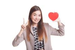 Signe asiatique de victoire d'exposition de femme d'affaires avec le coeur rouge Photographie stock libre de droits