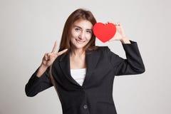 Signe asiatique de victoire d'exposition de femme d'affaires avec le coeur rouge Images libres de droits