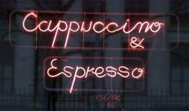 Signe au néon (cappuccino et café express) en dehors d'un café Image libre de droits