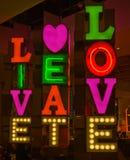 Signe au néon ; vivez, mangez, aimez. Photo stock