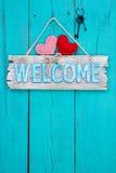 Signe bienvenu accrochant sur la porte en bois âgée Image libre de droits