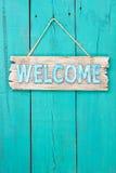 Signe bienvenu accrochant sur la porte en bois bleue de sarcelle d'hiver Image stock