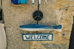 Signe bienvenu avec la baleine bleue accrochant sur le mur en pierre Photo libre de droits