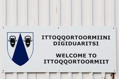 Signe bienvenu bilingue de village d'Ittoqqortoormiit photographie stock
