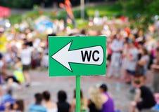 Signe blanc du cabinet d'aisance de flèche (carte de travail) contre la foule Photographie stock libre de droits