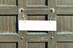 Signe blanc vide accrochant avec la corde déchirée en lambeaux sur le vieux mur en bois brun avec des rivets en métal - fond dans Images stock